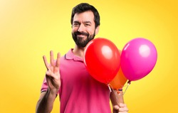 Handsome young man holding balloons and counting three on colorful background