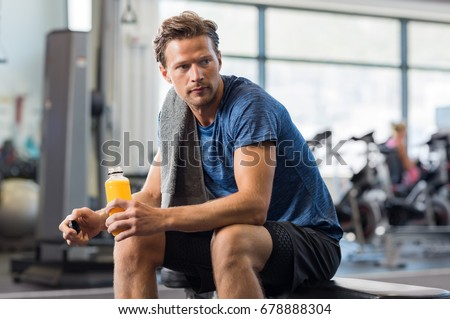 Handsome young man holding bottle of fresh orange juice while resting at gym.Thoughtful fit man sitting alone holding a bottle of energy drink. Guy take break after fitness exercise on bench.