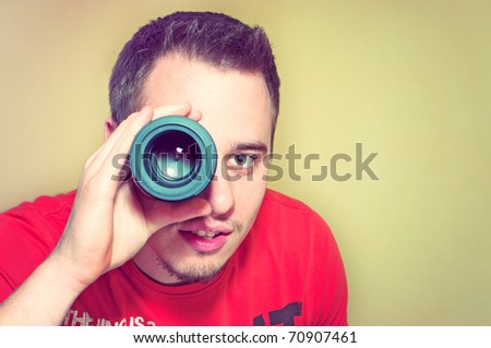 Handsome young man holding camera lens like it was spyglass