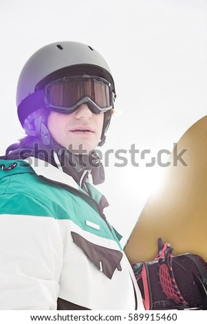 Handsome young man holding snowboard outdoors #589915460