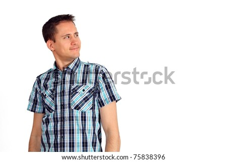 Handsome young man in a blue shirt looking up to the right