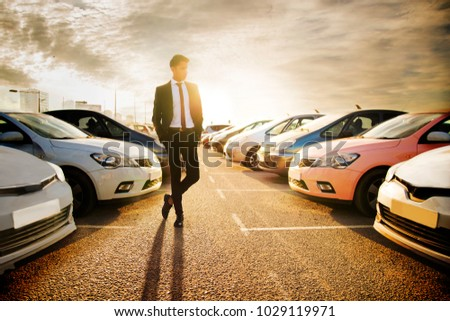 Handsome young man in a business suit choosing a car in the car market #1029119971