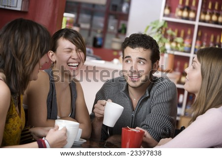 Handsome young man in a coffee house surrounded by pretty women