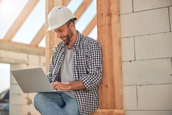 Handsome young man in a hard hat looking at laptop screen while sitting outside the construction site