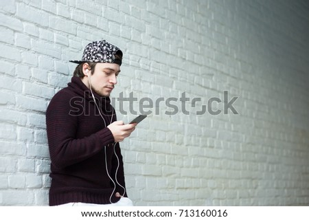 fd6d37aaa60 Handsome young man in a woolen sweater and cap with a smartphone and in  headphones against