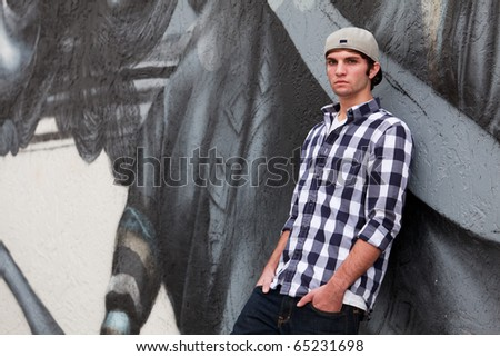 Handsome young man in an urban fashion lifestyle pose leaning on a graffiti wall wearing a baseball cap.