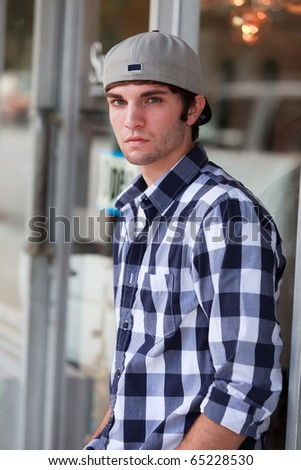 Handsome young man in an urban lifestyle fashion pose leaning against a store front wearing a baseball hat.