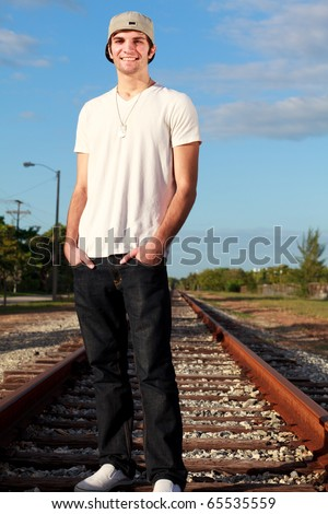 Handsome young man in an urban lifestyle fashion pose standing on a railroad track.