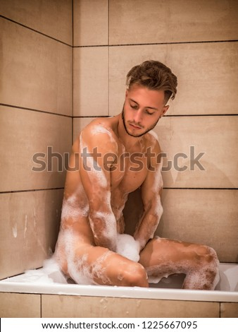 Handsome young man in bathtub at home having bath, sitting on tub edge,