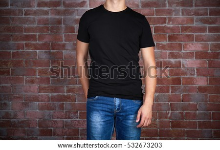 Handsome young man in blank black t-shirt standing against brick wall, close up #532673203