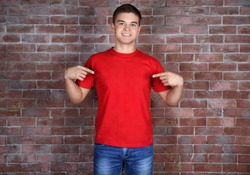 Handsome young man in blank red t-shirt standing against brick wall