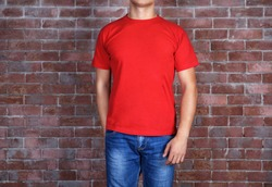 Handsome young man in blank red t-shirt standing against brick wall, close up