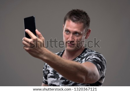 Handsome young man in camouflage pattern t-shirt taking photos with mobile phone on gray background.