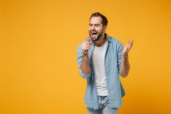 Handsome young man in casual blue shirt posing isolated on yellow orange wall background, studio portrait. People lifestyle concept. Mock up copy space. Sing song in microphone, keeping eyes closed