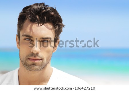 Handsome young man in casual white top against bright beach background