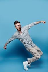 Handsome young man in glasses dancing in studio
