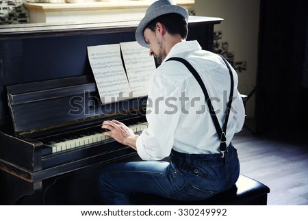 Handsome young man in hat making piano music