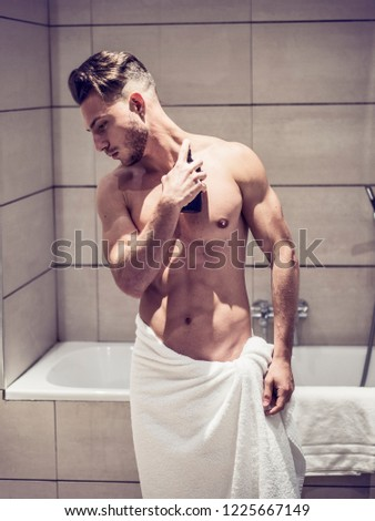 Handsome young man in his home bathroom, spraying cologne or perfume on neck