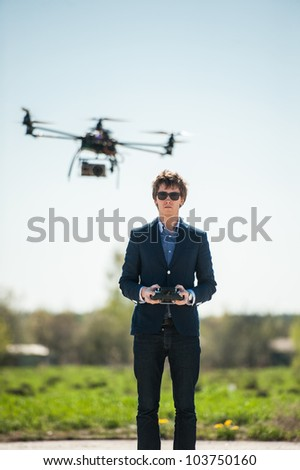 Handsome young man in suit flying remote controlled helicopter in countryside.