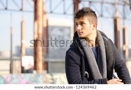 Handsome young man in urban or industrial setting looking to a side. Large copy-space.