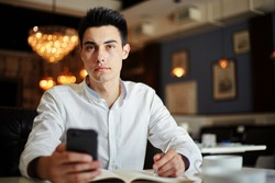 Handsome young man in white shirt sitting at table in modern cafe holding phone and writing in notepad looking at camera