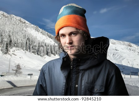 Handsome young man in winter clothes and mountains in the background