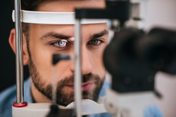 Handsome young man is checking the eye vision in modern ophthalmology clinic. Patient in ophthalmology clinic