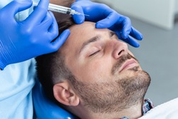 Handsome young man is getting a rejuvenating facial injections. He is sitting calmly at clinic. The expert beautician is filling male wrinkles by hyaluronic acid.