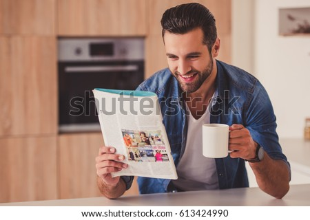 Handsome young man is holding a cup, reading magazine and smiling while resting in kitchen