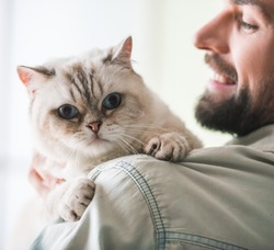 Handsome young man is holding a cute cat, looking at it and smiling