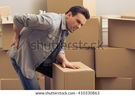 Handsome young man is moving, having pain in his back while packing, standing among cardboard boxes