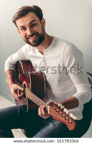 Handsome young man is playing guitar  looking at camera and smiling  on gray background
