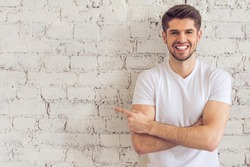Handsome young man is pointing away, looking at camera and smiling, standing against white brick wall