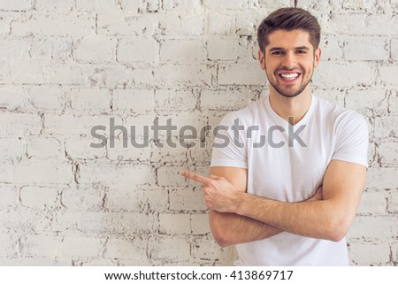 Handsome young man is pointing away, looking at camera and smiling, standing against white brick wall #413869717