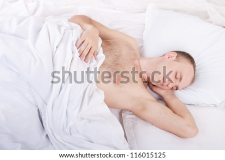 handsome young man is sleeping in bed with white linen