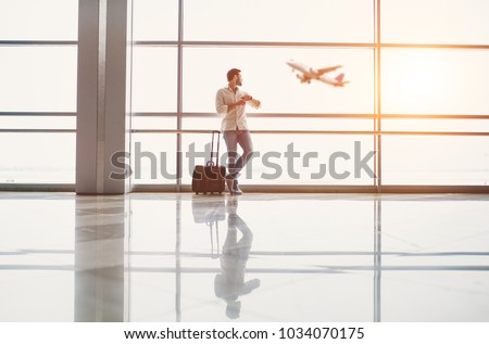 Handsome young man is standing near the panoramic window in airport terminal with suitcase while waiting for the flight.