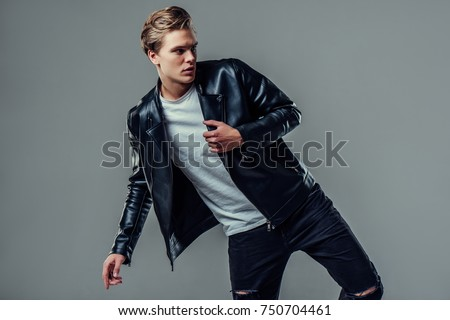 Handsome young man isolated. Fashionable  man in leather jacket is standing on grey background.