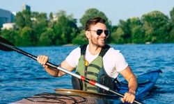 Handsome young man kayaking on a lake. Happy guy canoeing in a lake. Kayaking. Man paddling a kayak. Concept for adventure, travel, action, lifestyle