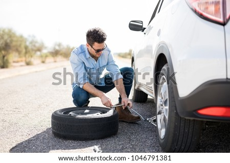 Handsome young man lifting the car on the jack for changing flat tire on the road #1046791381