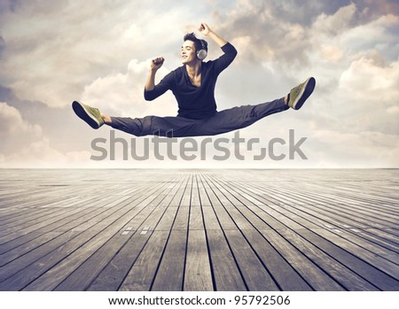 Handsome young man listening to music and dancing on a parquet floor