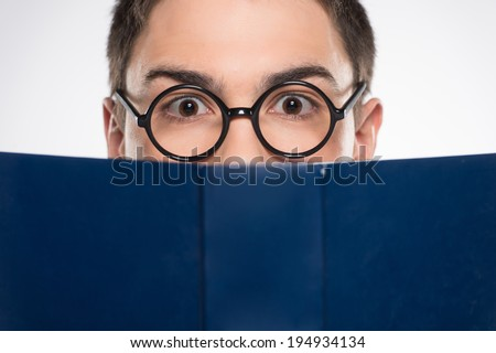 handsome young man looking ahead. attractive male reading blue book