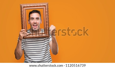Handsome young man looking through vintage art frame screaming proud and celebrating victory and success very excited, cheering emotion