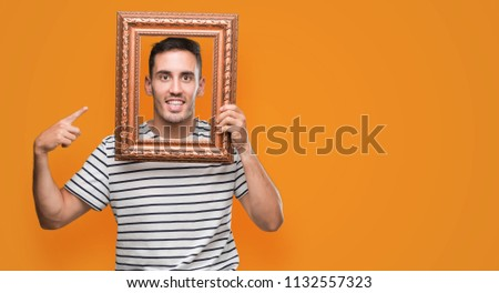 Handsome young man looking through vintage art frame very happy pointing with hand and finger