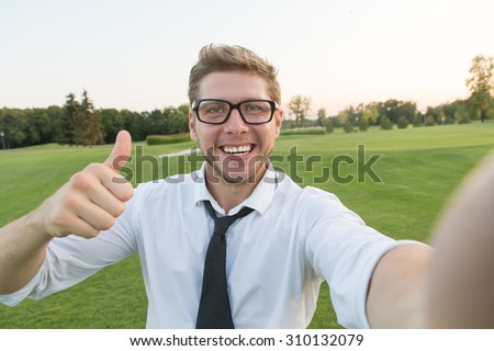 Handsome young man making a selfie picture with smart phone. Blond man showing okay sign and white teeth. He is communicating with foreign friends.