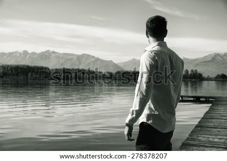 Handsome young man on a lake\'s shore in a sunny, peaceful day, standing. Black and white shot