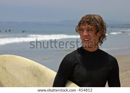 handsome young man on beach after surfing