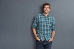 Handsome young man on grey background looking at camera. Portrait of laughing young man with hands in pockets leaning against grey wall. Happy guy smiling.