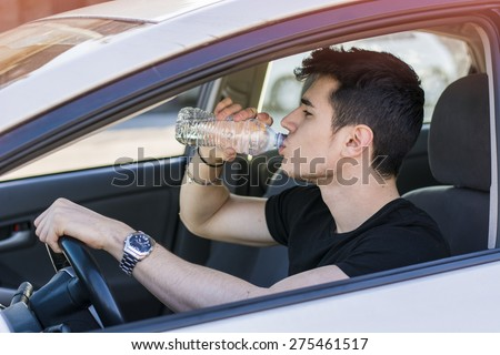 Handsome young man or teenager driving car and drinking water from plastic bottle