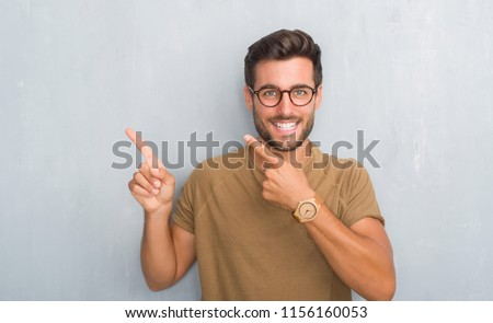 Handsome young man over grey grunge wall wearing glasses smiling and looking at the camera pointing with two hands and fingers to the side. #1156160053