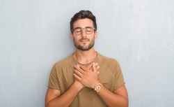 Handsome young man over grey grunge wall wearing glasses smiling with hands on chest with closed eyes and grateful gesture on face. Health concept.